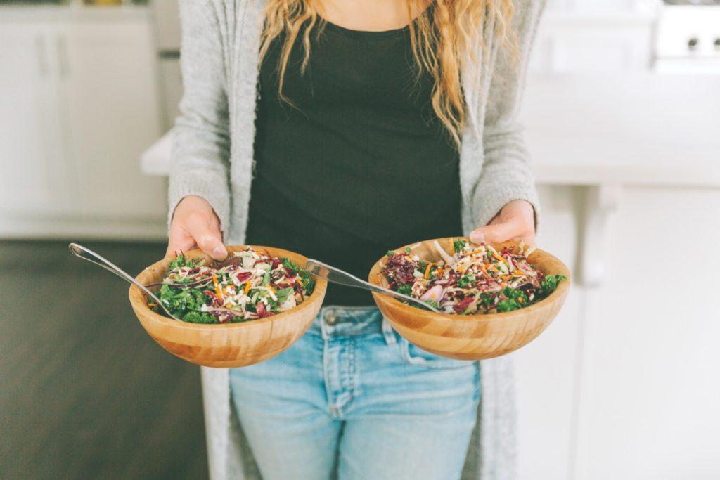 a woman holding two salads t20 Rz8WYm