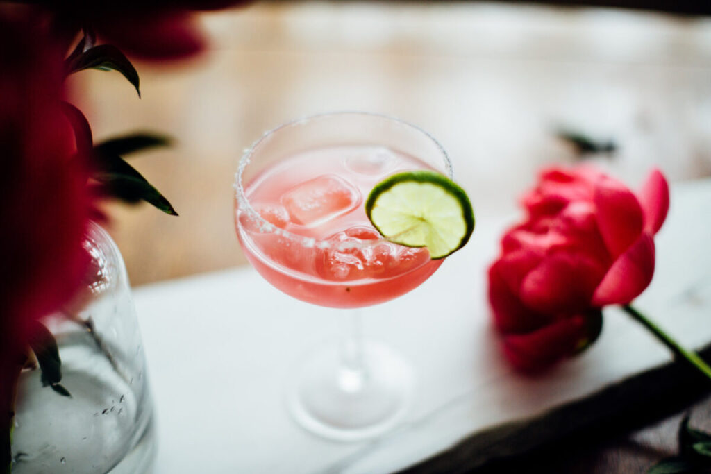 grapefruit and blood orange margarita sits in a coupe glass with flowers and a lime as garnish t20 Zz12Zo